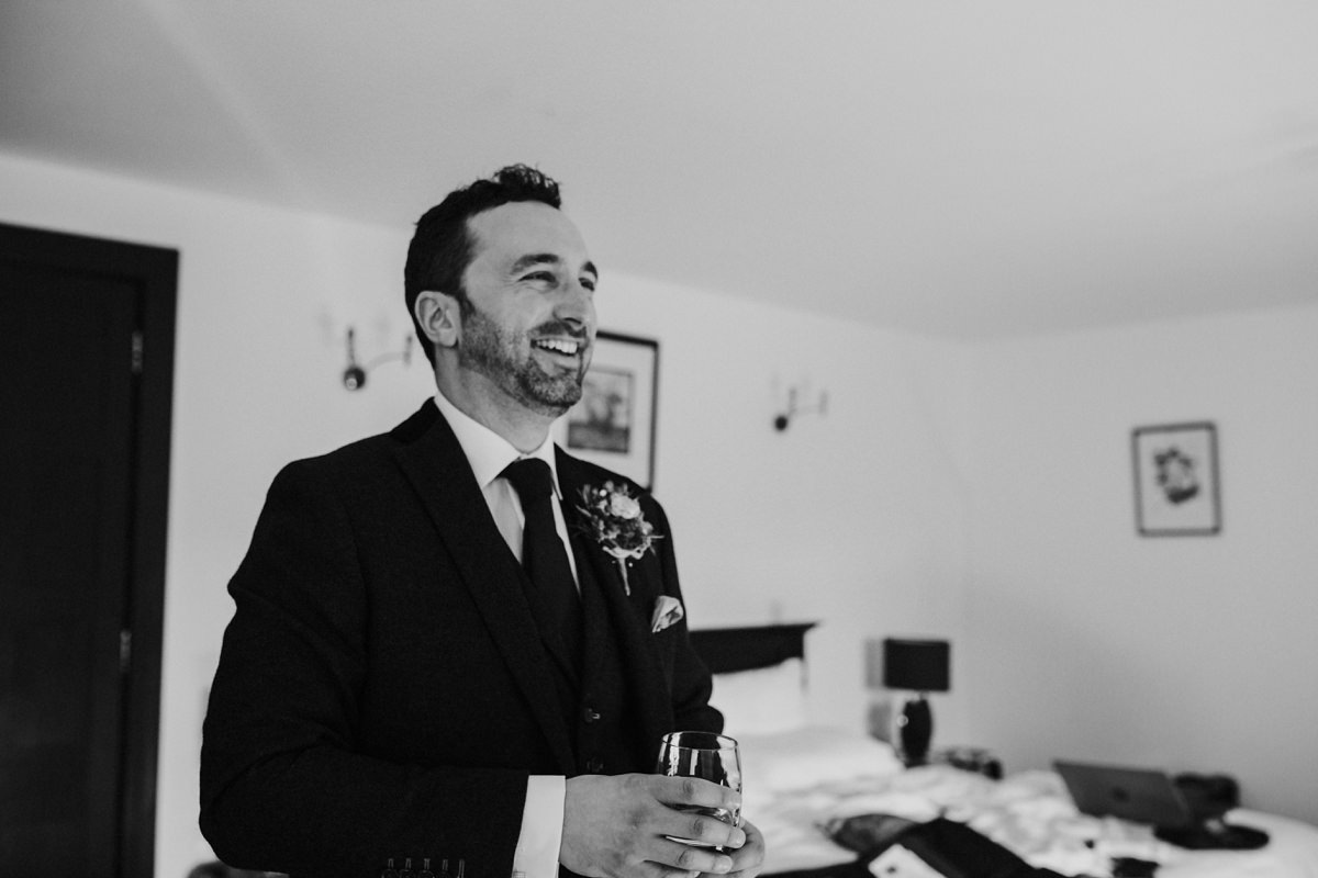 black and white of groom laughing getting ready