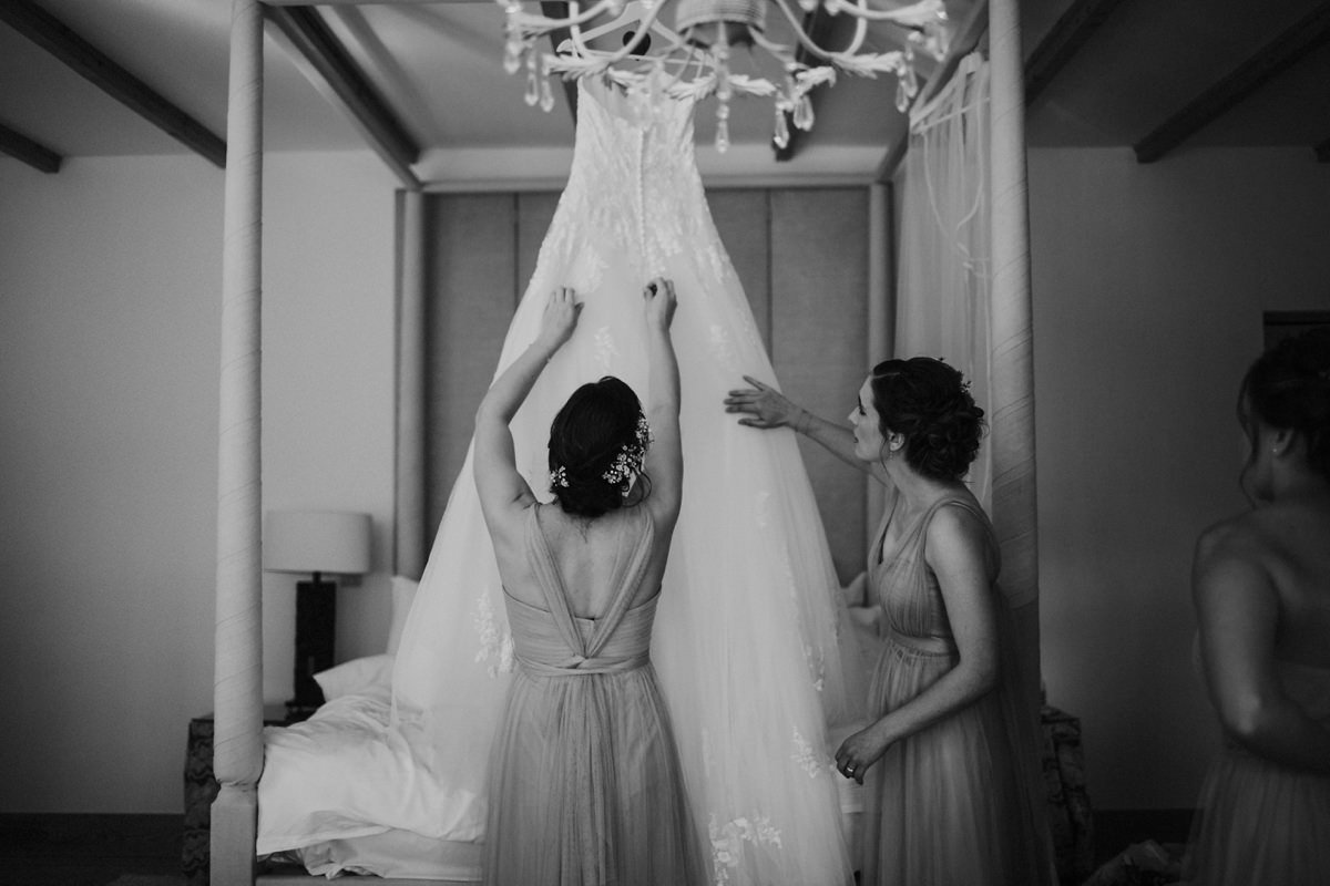 black and white of bridesmaids helping with bride's dress