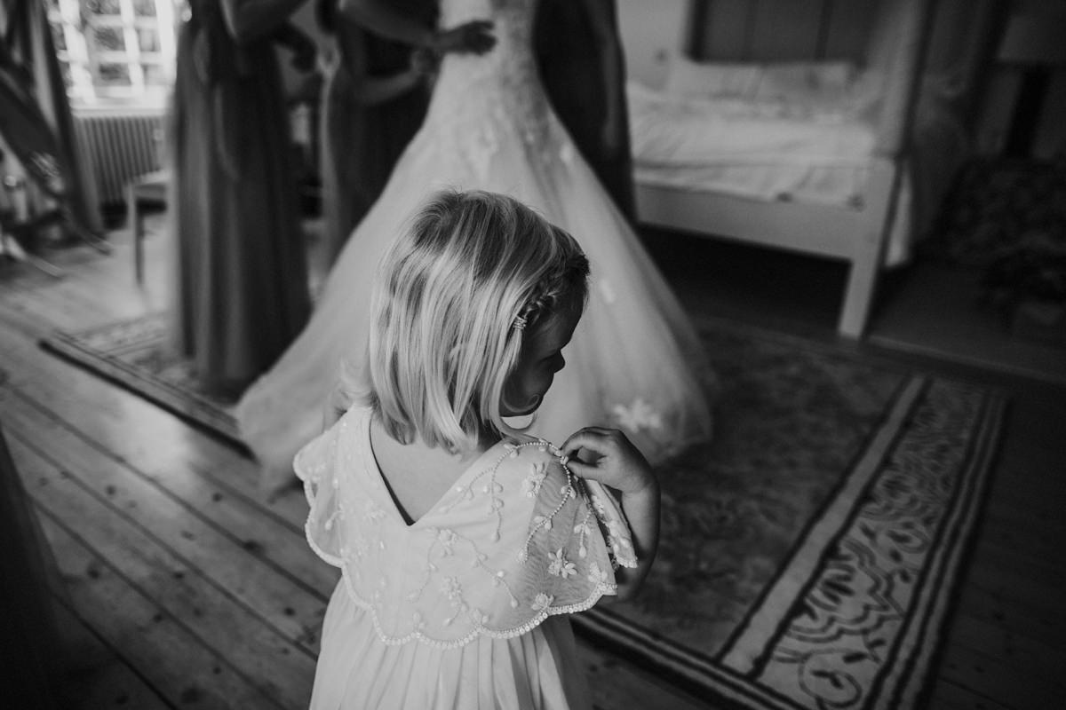 black and white of flower girl getting ready in her monsoon dress