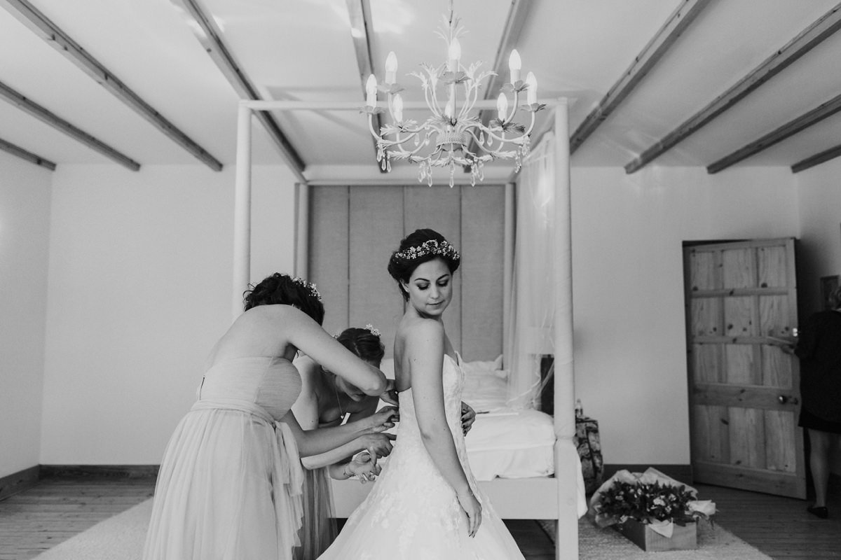 black and white of bridesmaids helping the bride into her dress at Achnagairn house
