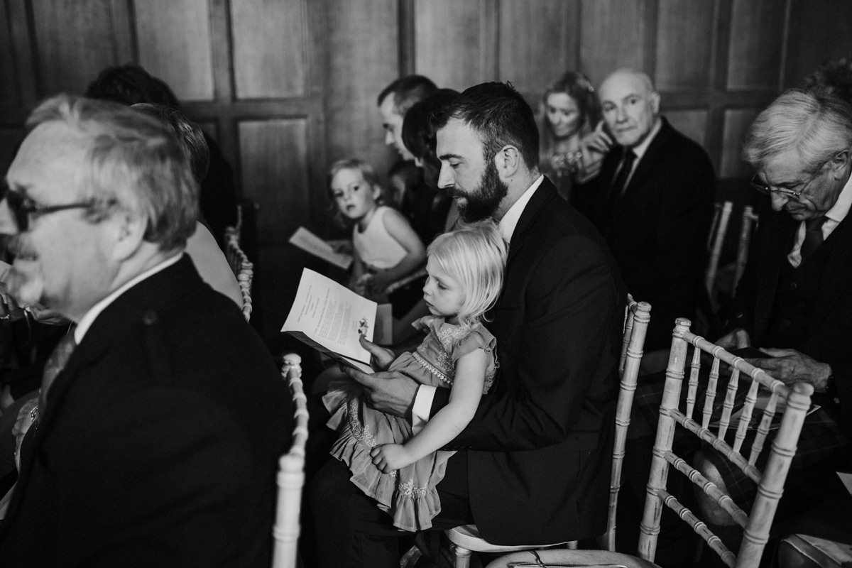 black and white of guests reading order of service before the ceremony starts
