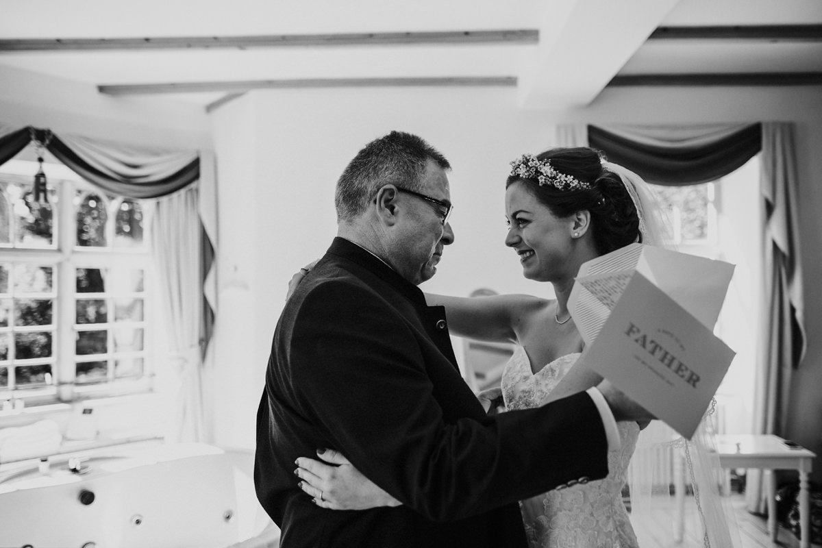 black and white of bride and father having an emotional moment before the ceremony