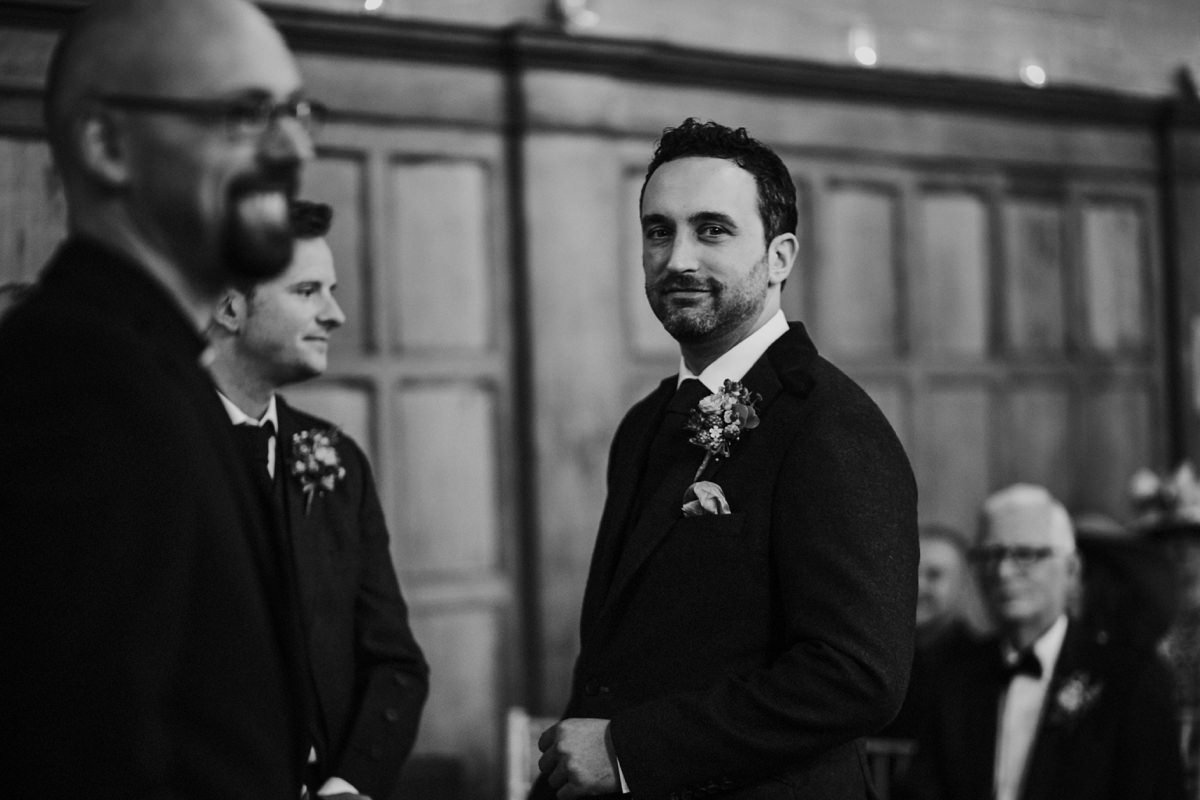 black and white of nervous groom waiting at the top of the aisle