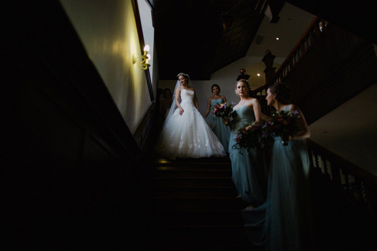 Bride on the stairs at Achnagairn house with her bridesmaids