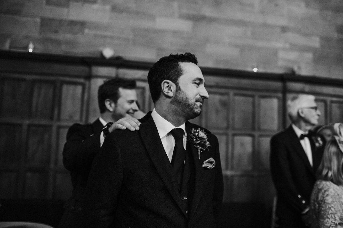 Groom being reassured by best man getting emotional as bride walks towards him