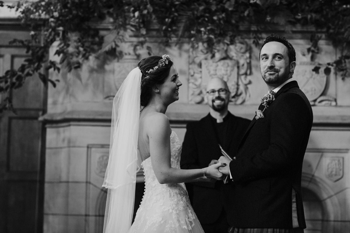 black and white of proud bride and groom during ceremony