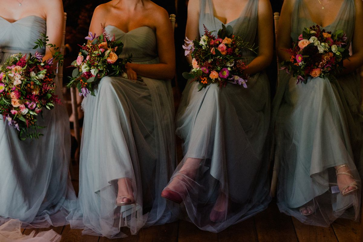 Image of bridesmaids waiting during ceremony with colourful woodland bouquets