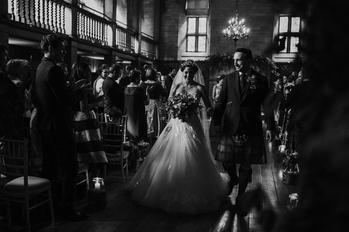 Black and White of bride and groom walking down the aisle as a married couple at Achnagairn Castle