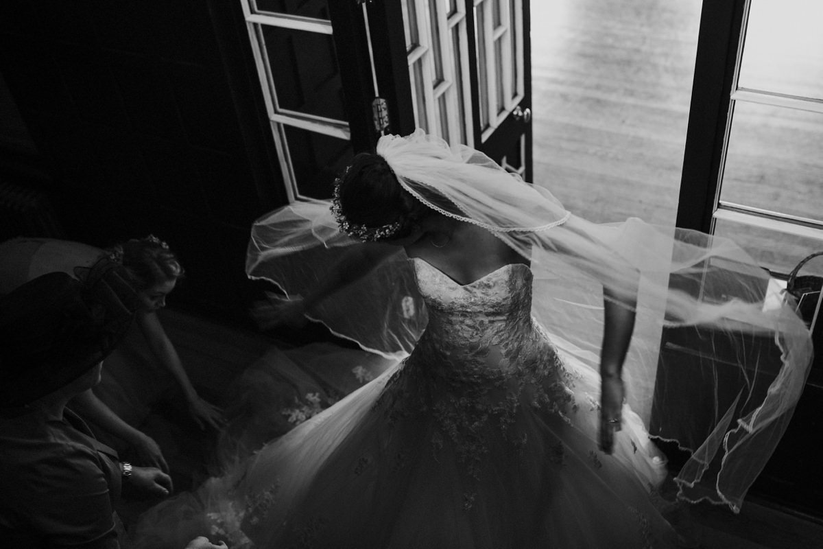 Black and White of Bride sorting her dress before her entrance