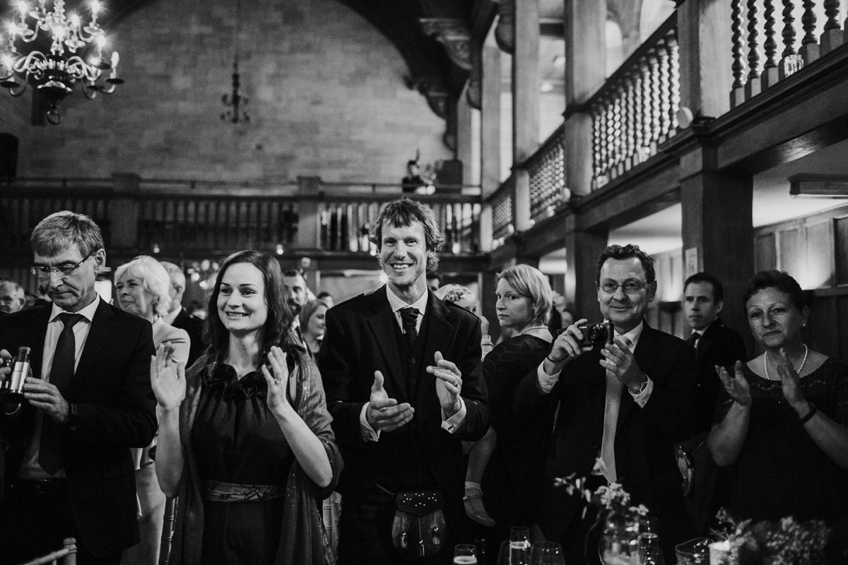 Guests clapping at entrance of bride and groom at wedding meal