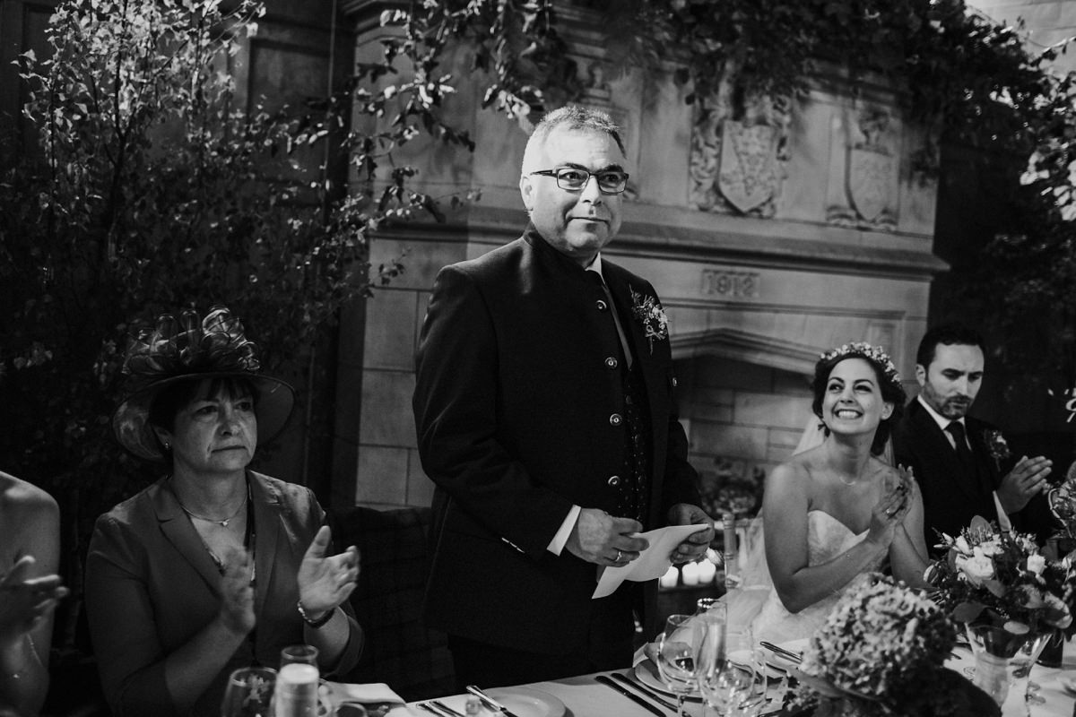 Black and white of proud father of the bride doing a speech