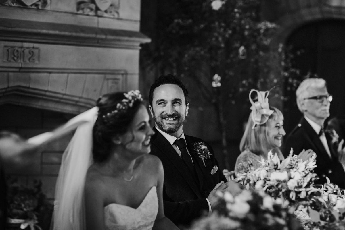 black and white of smiling groom during speeches