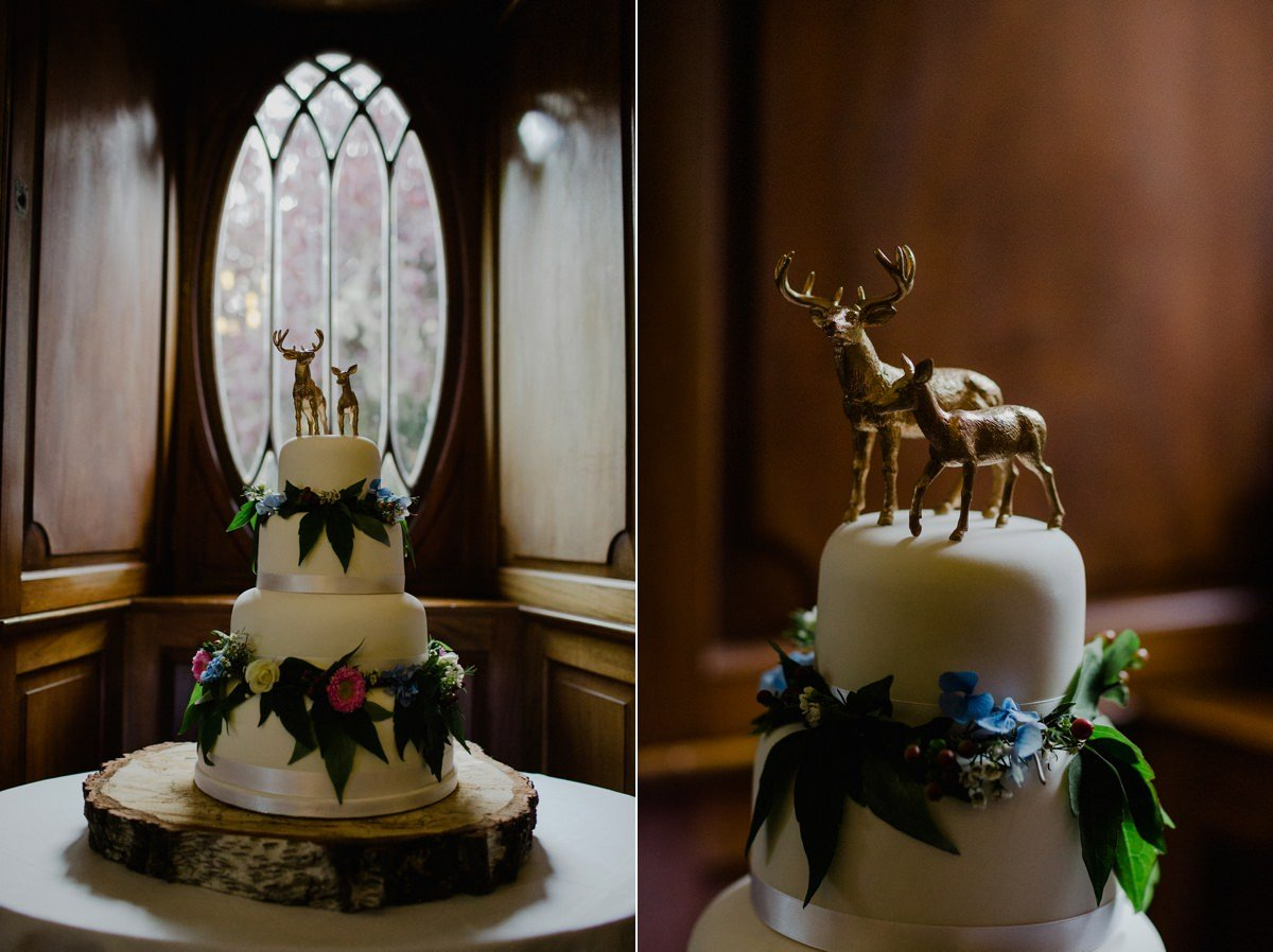 woodland inspired wedding cake in window with stag and doe as toppers