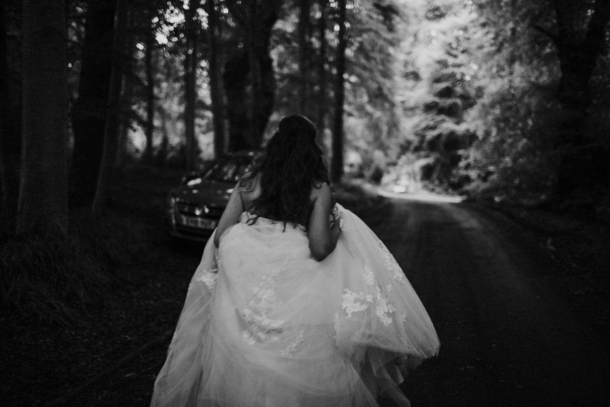 Moody black and white of bride walking through the woodland