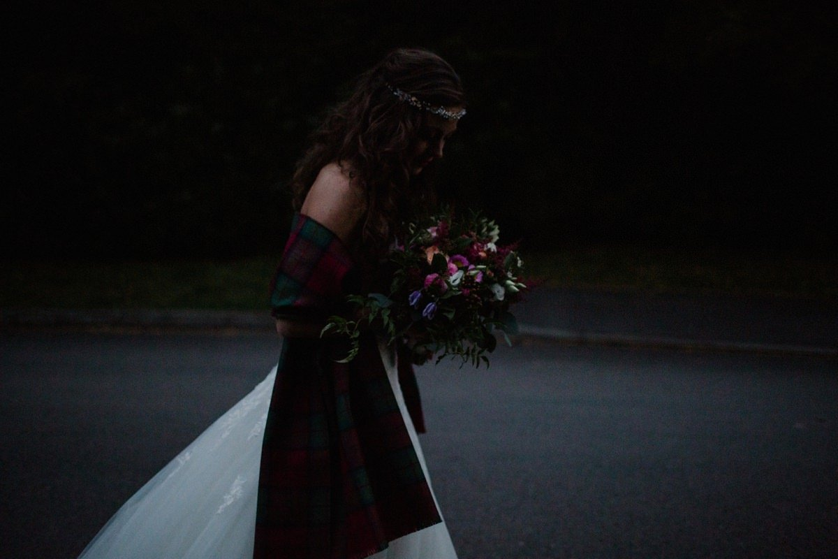 Dark, moody image of bride walking