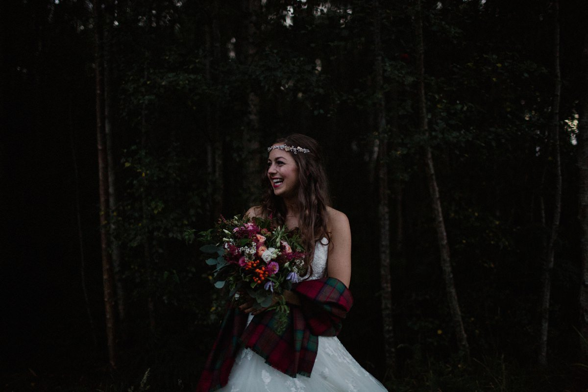 Happy smiling bride with tartan shawl in the woodland at twilight