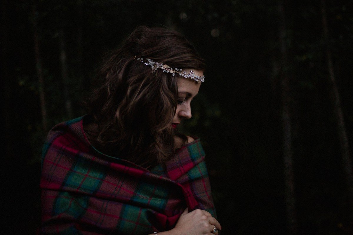 Moody image of bride cuddling into her tartan shawl to keep warm