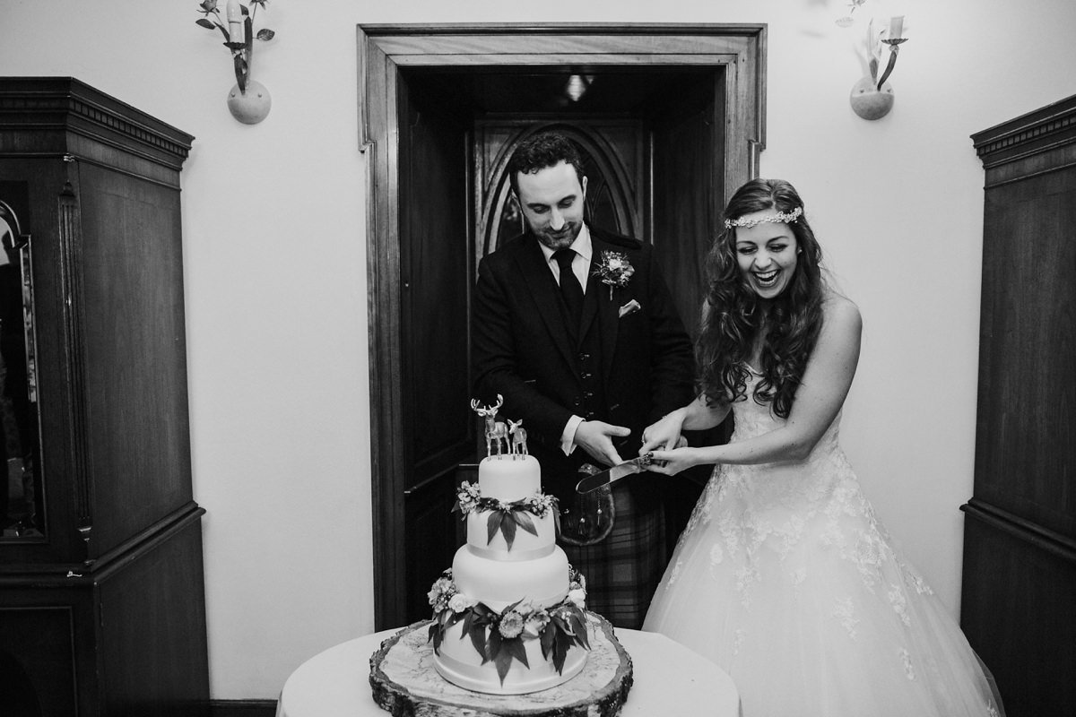 bride and groom laughing cutting the cake