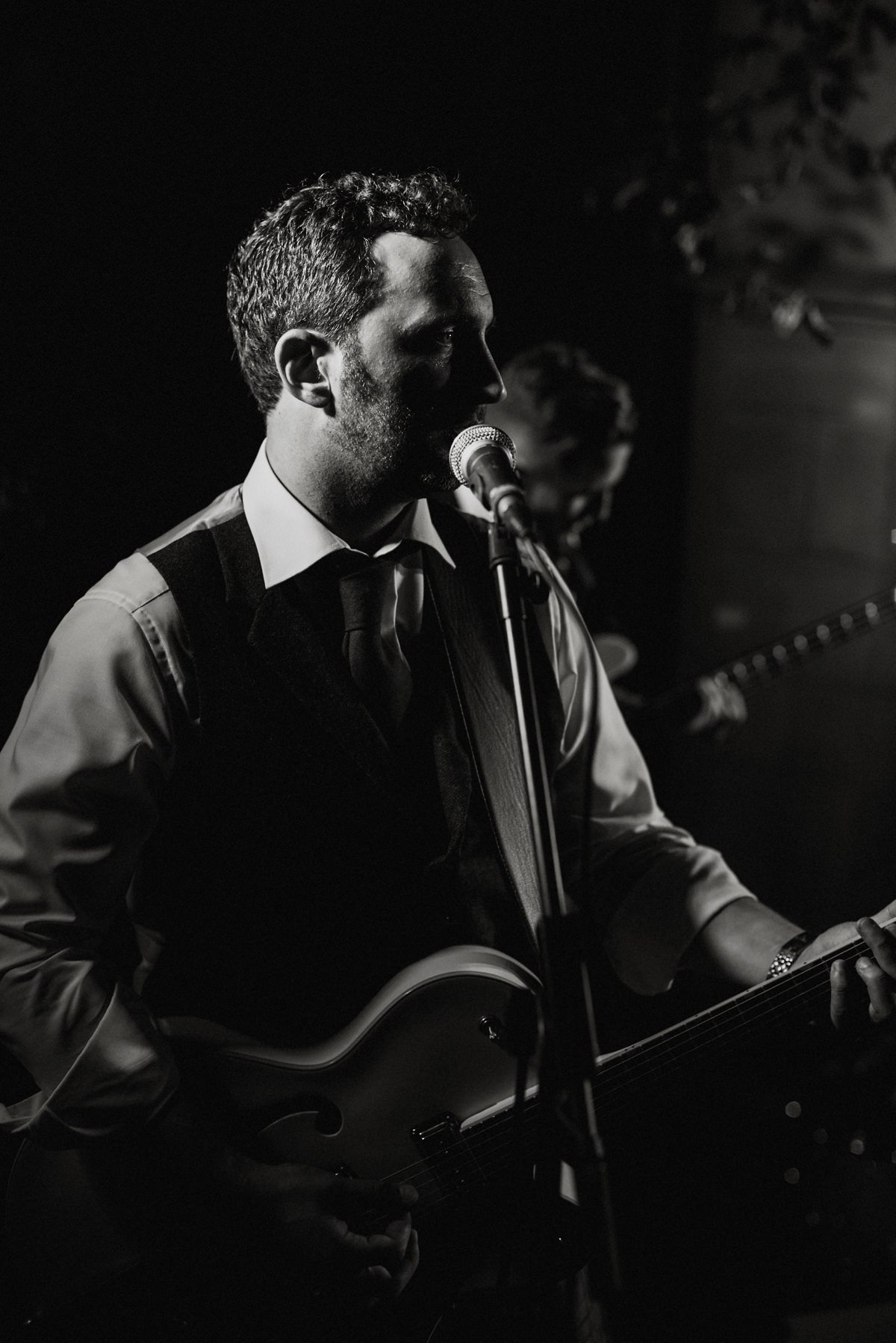 Closeup of groom singing and playing guitar in his band