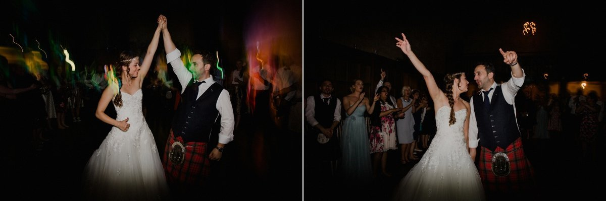 bride and groom celebrating and dancing with hands in the air