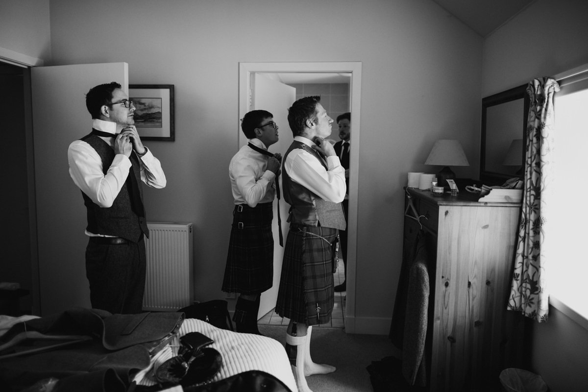 Men putting on their ties ready for the wedding