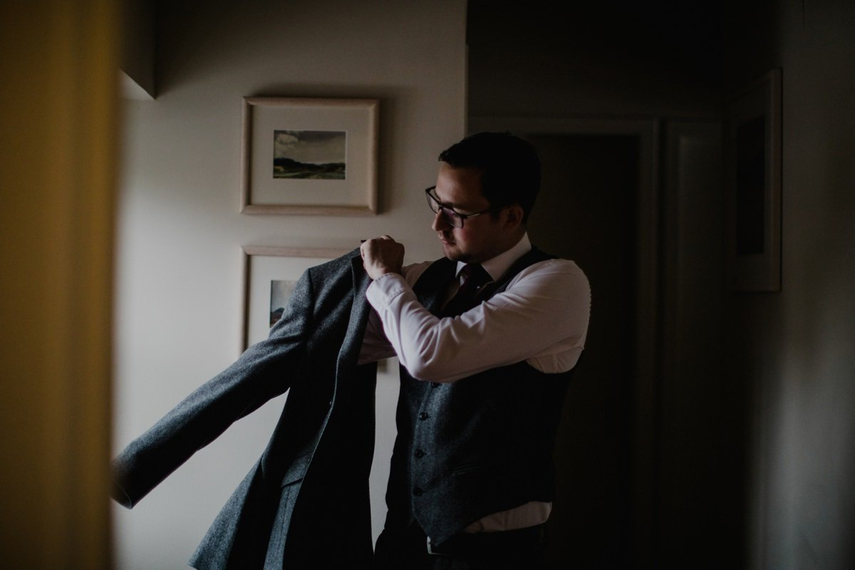 Groom putting on his suit jacket by the window