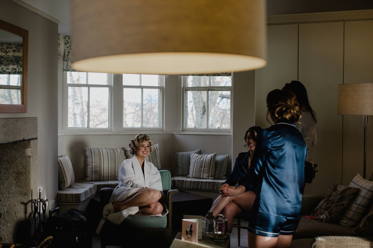 Bride laughing with her girls on the morning of her wedding