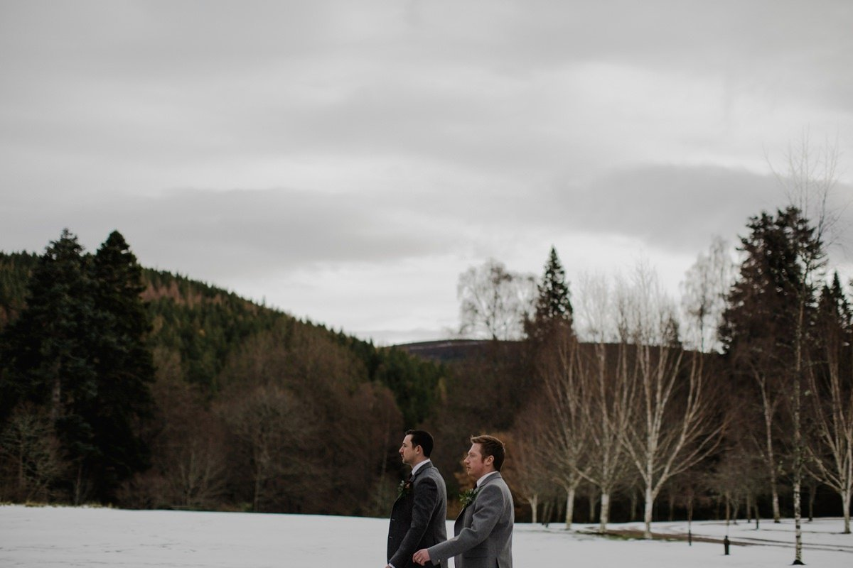 Groom and best man walk to the ceremony together through the snow