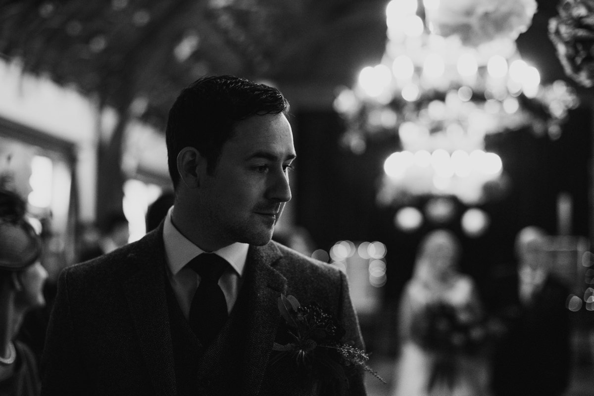 black and white of groom waiting for his bride, who can be seen in the background behind him