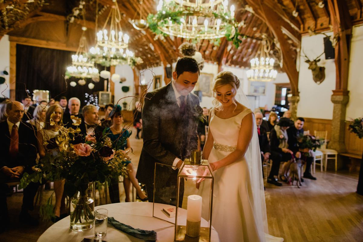 Couple lighting the candle during their wedding ceremony at Glen Tanar