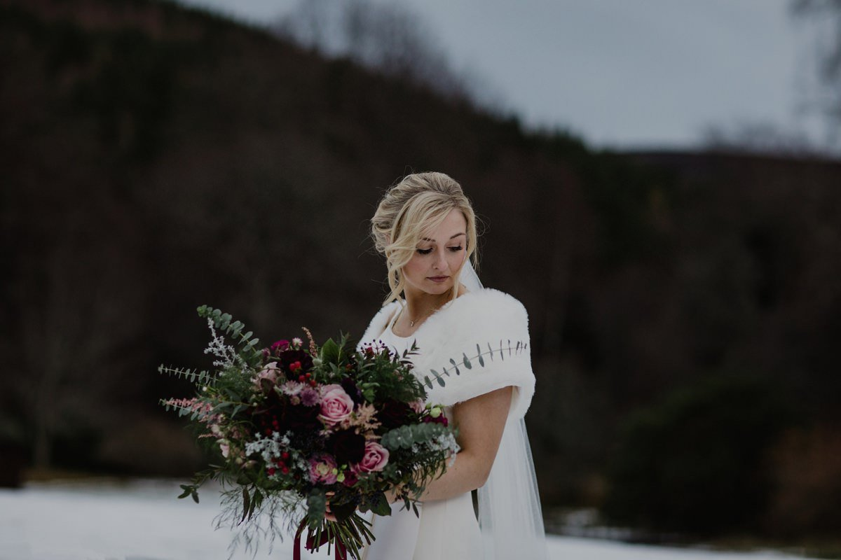 Snowy winter portrait of bride with fur stole and rustic bouquet at Glen Tanar Ballroom