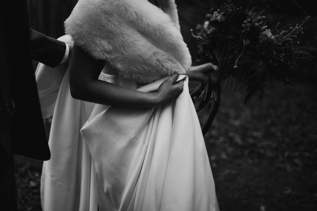 Black and White of bride with fur stole holding her dress up to walk