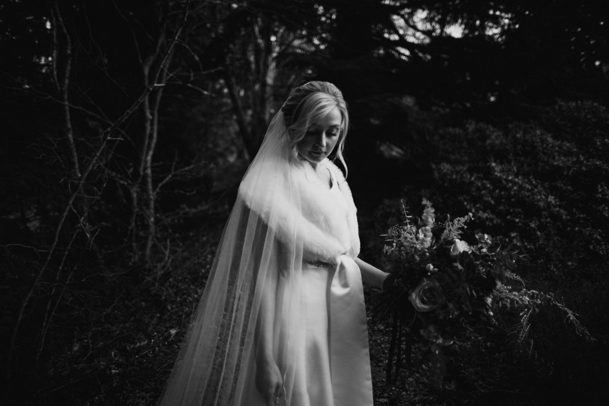 Black and White of bride in the woodland