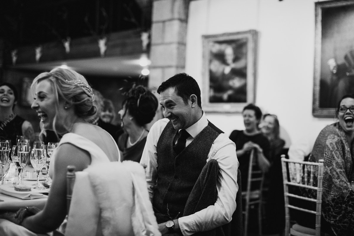 Black and White of Bride and Groom laughing during speeches