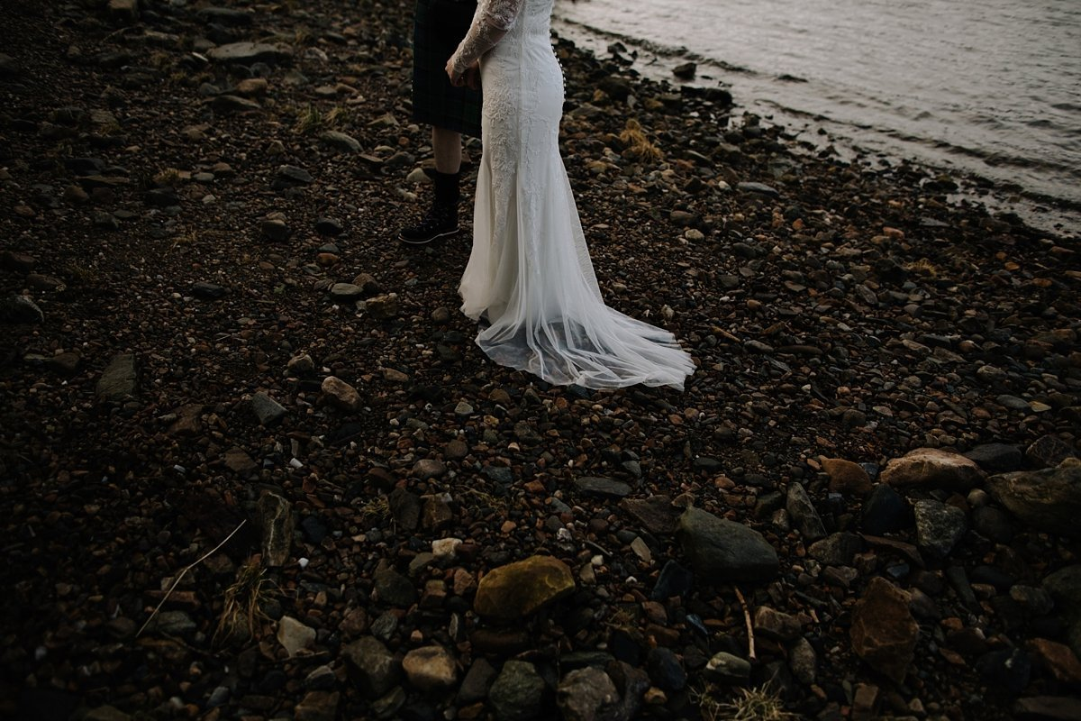Detail of brides dress on the beach by loch tay