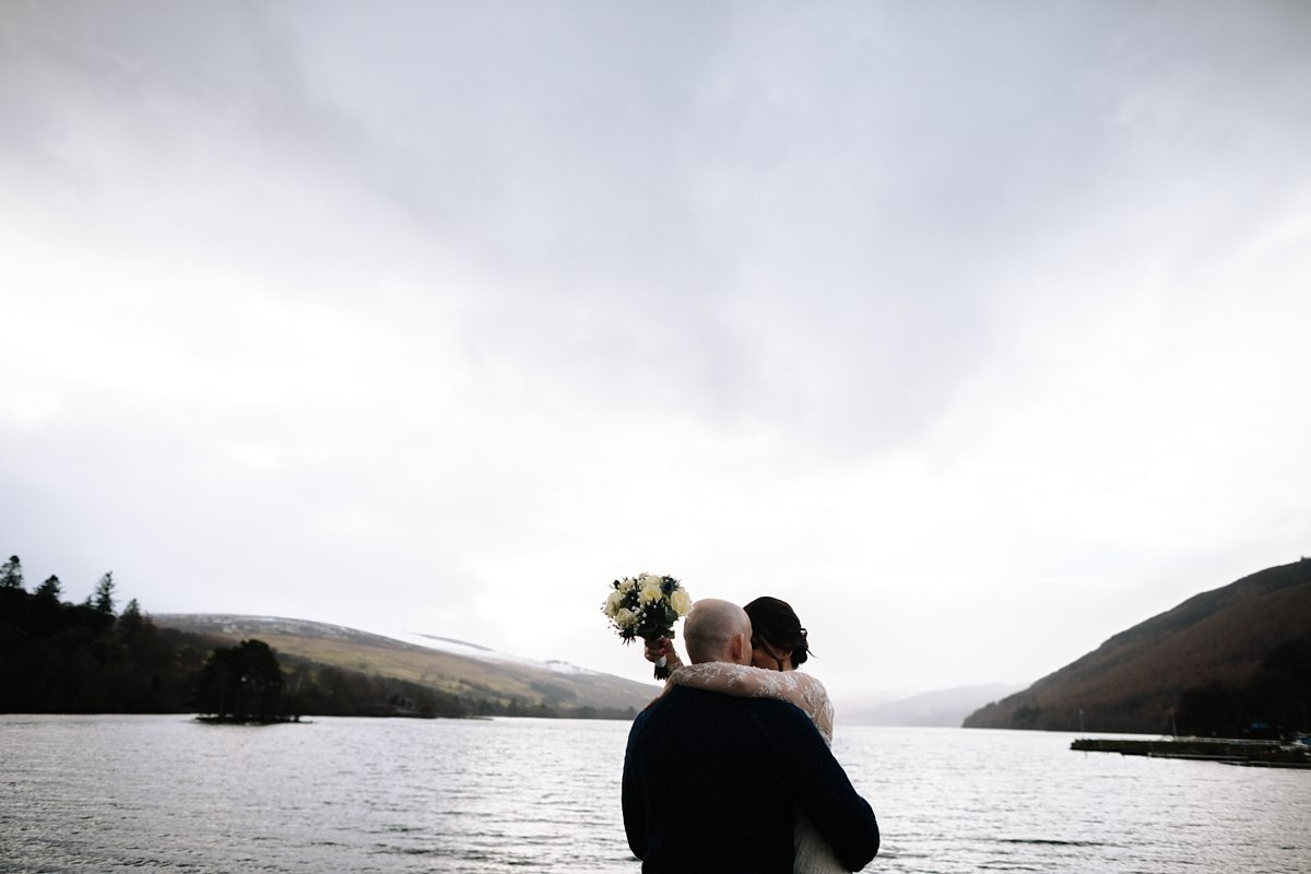 bride and groom in an embrace with views of loch tay