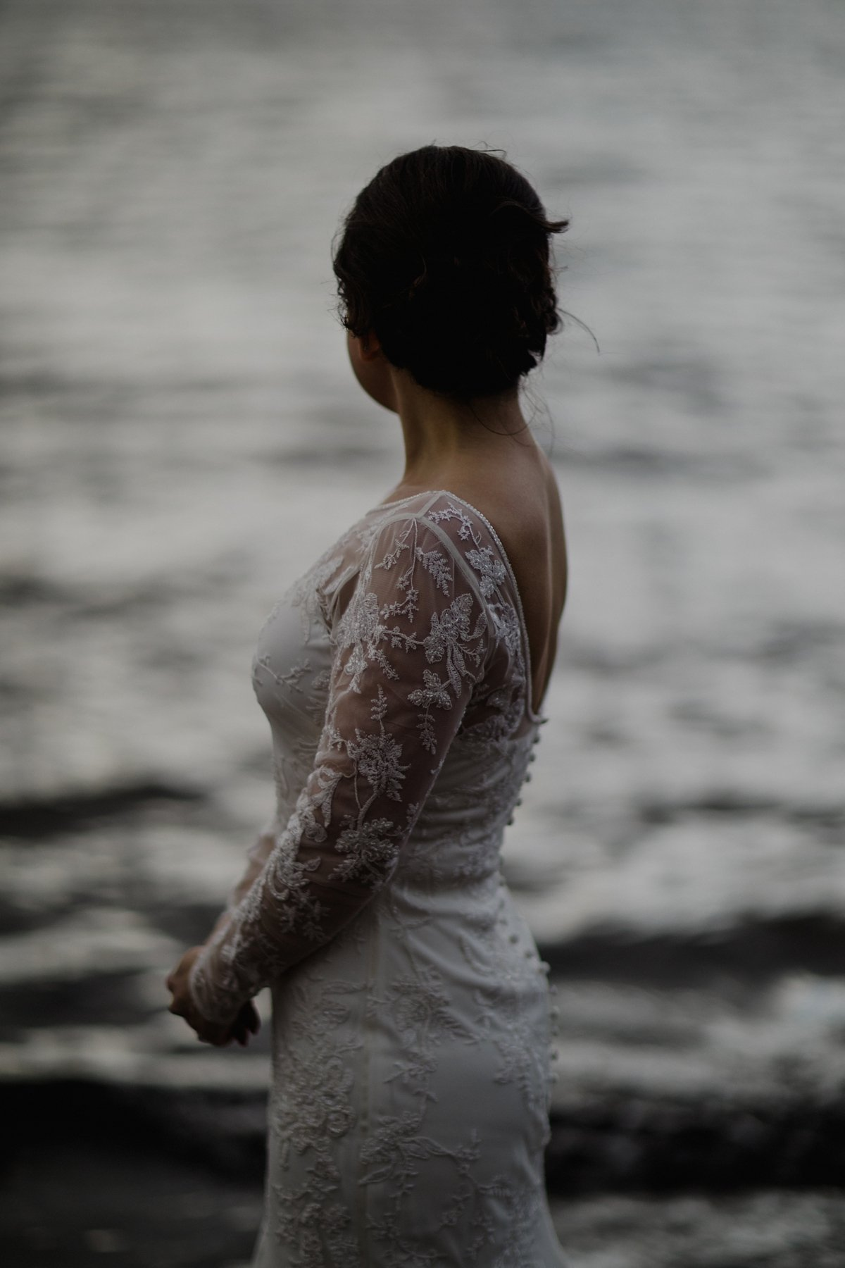 Atmospheric portrait of bride by the water