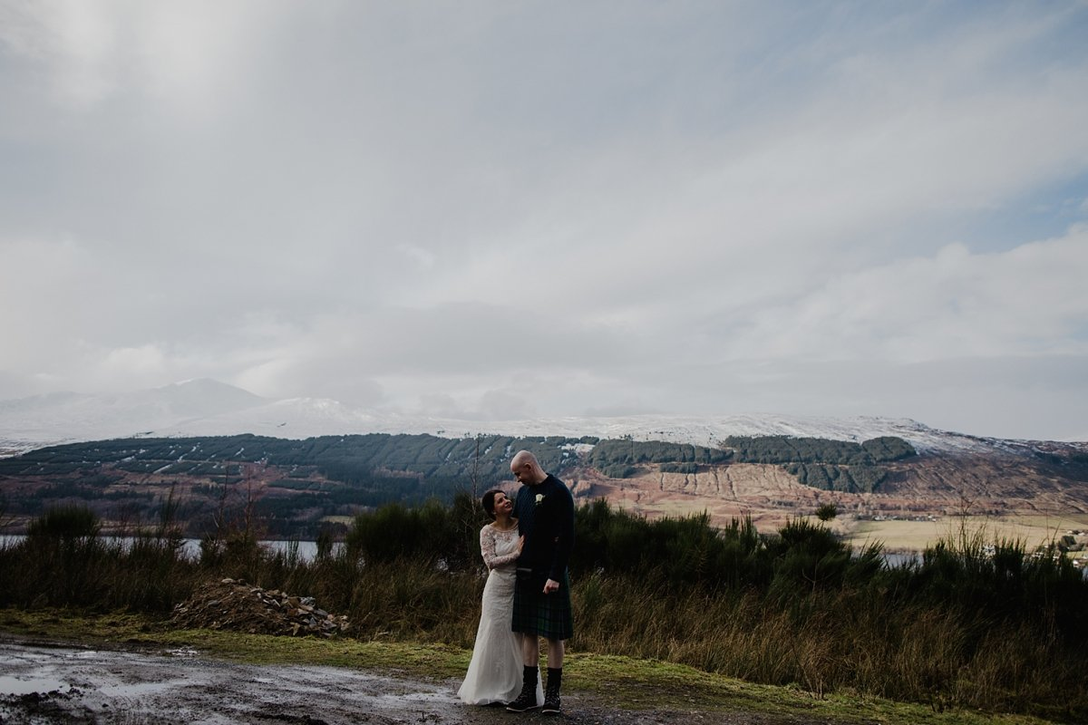 bride and groom in front of snowy scenery