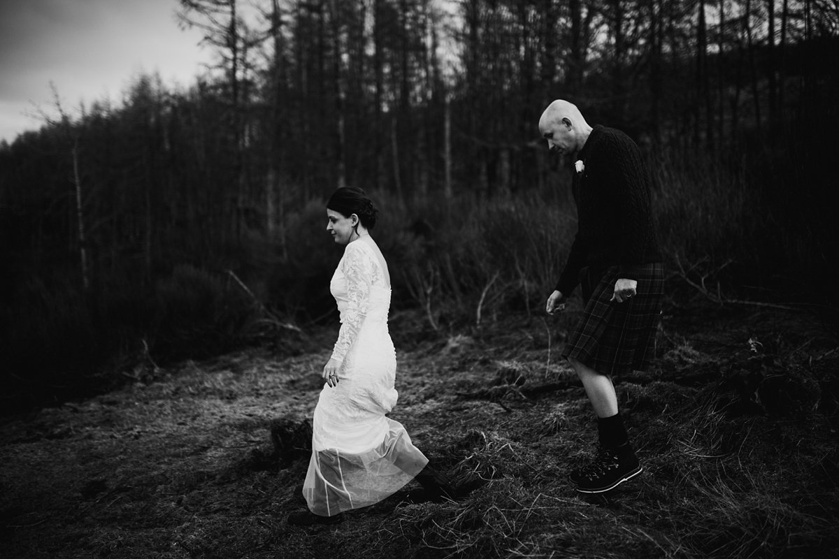 black and white of bride and groom walking through the forest