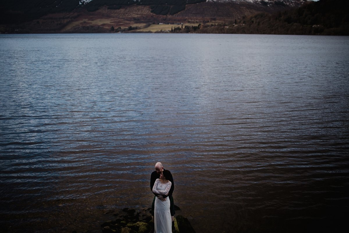 image of bride and groom with loch as backdrop