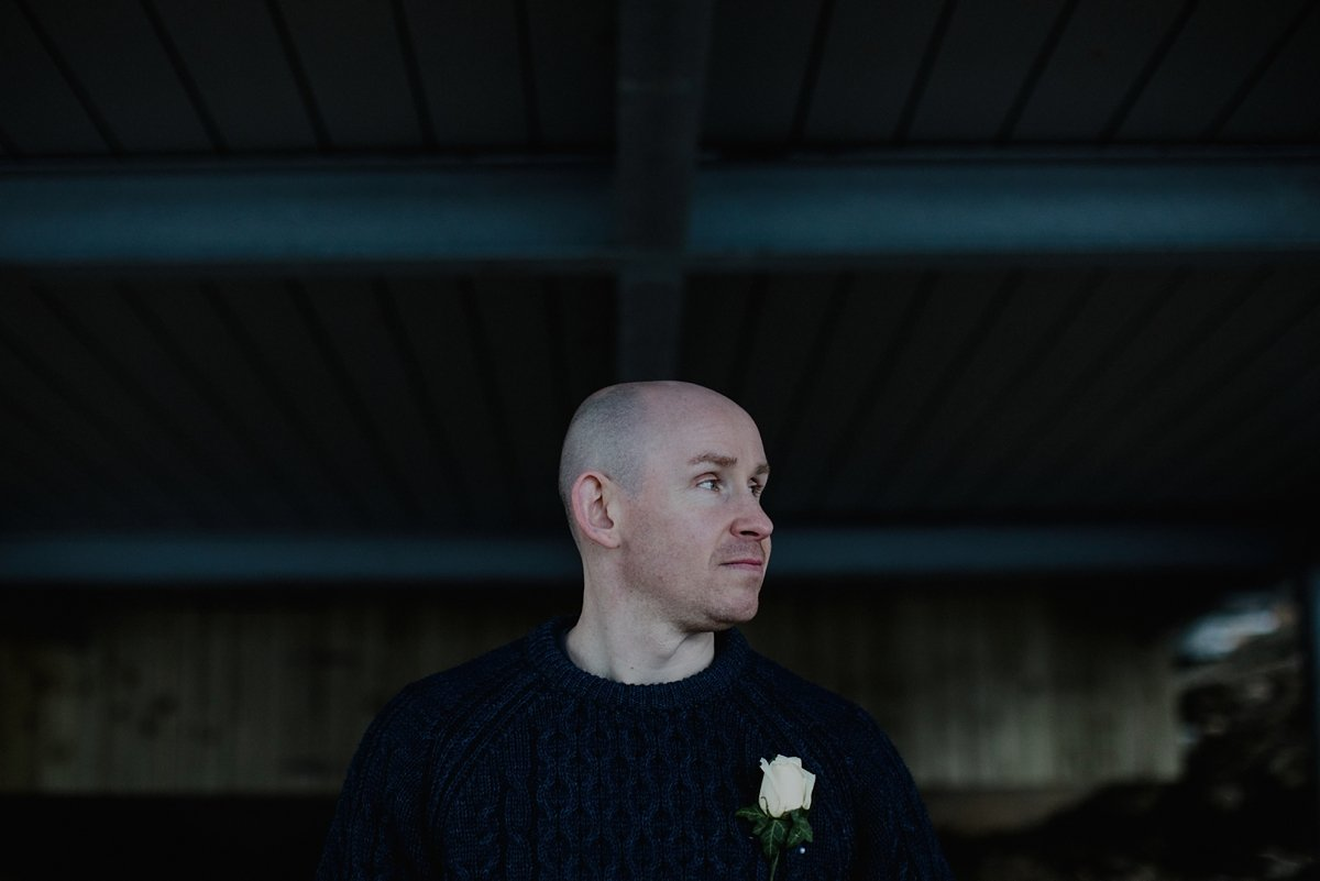 portrait of groom under the oyster boathouse
