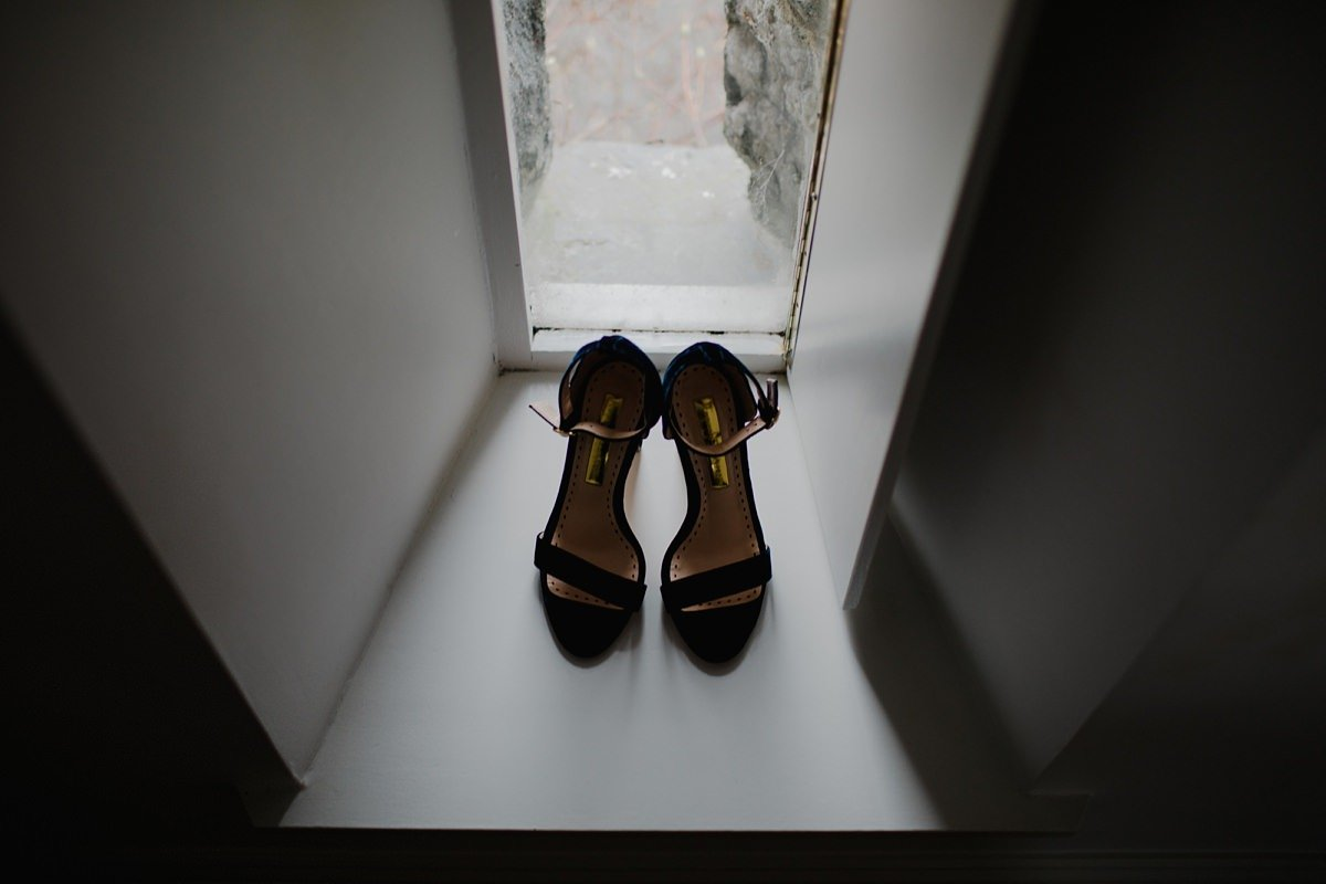 Bride's wedding shoes in the window of her bedroom at monachyle mhor hotel