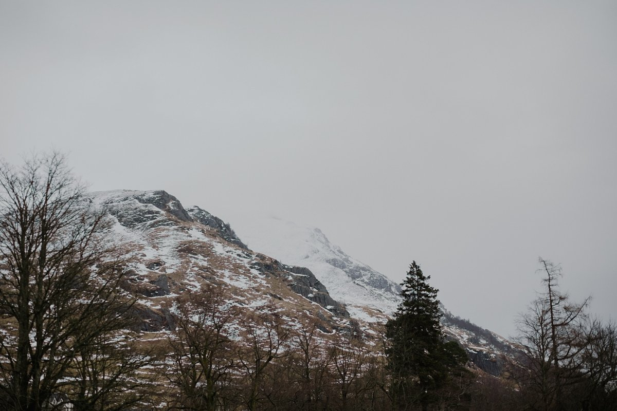 view of the trossachs hills dusted with snow from monachyle mhor hotel