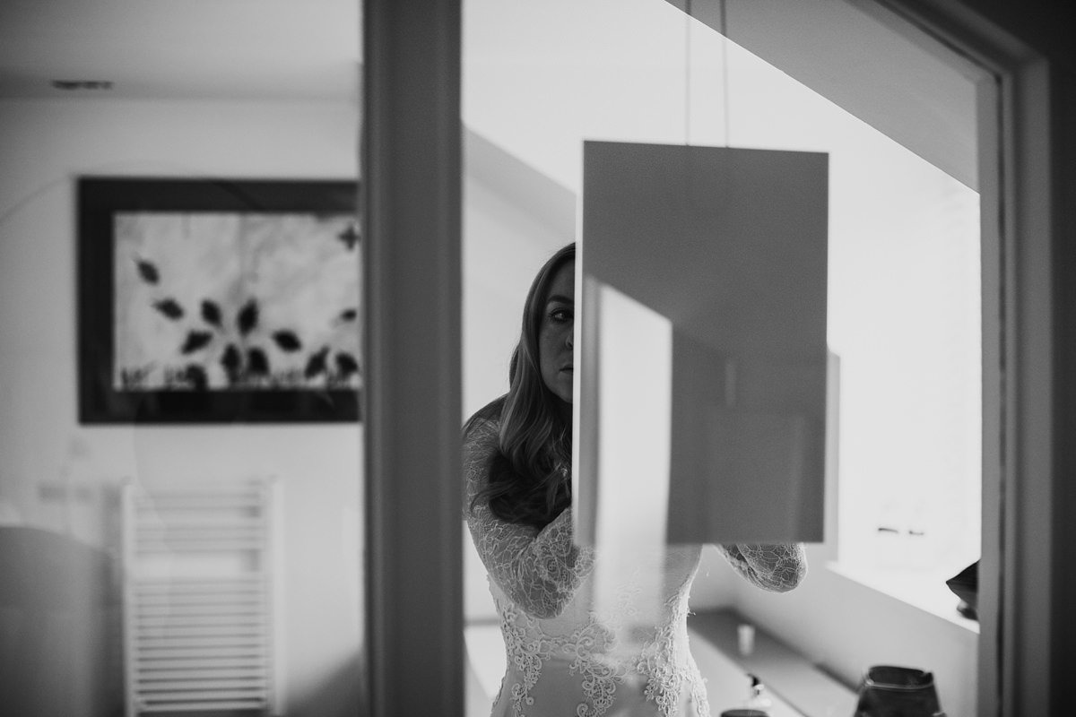 bride doing the final touches to her makeup in the mirror
