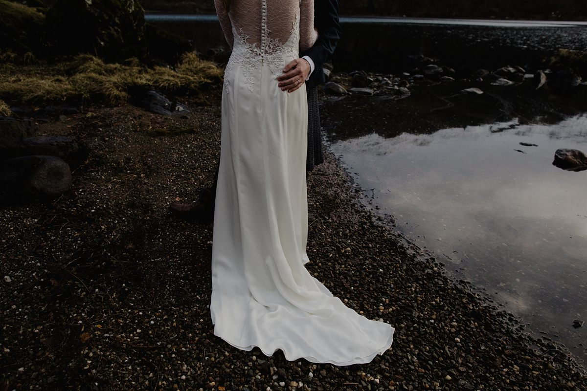 view of the back of the bride's dress with sheer back and button detail on the lochside