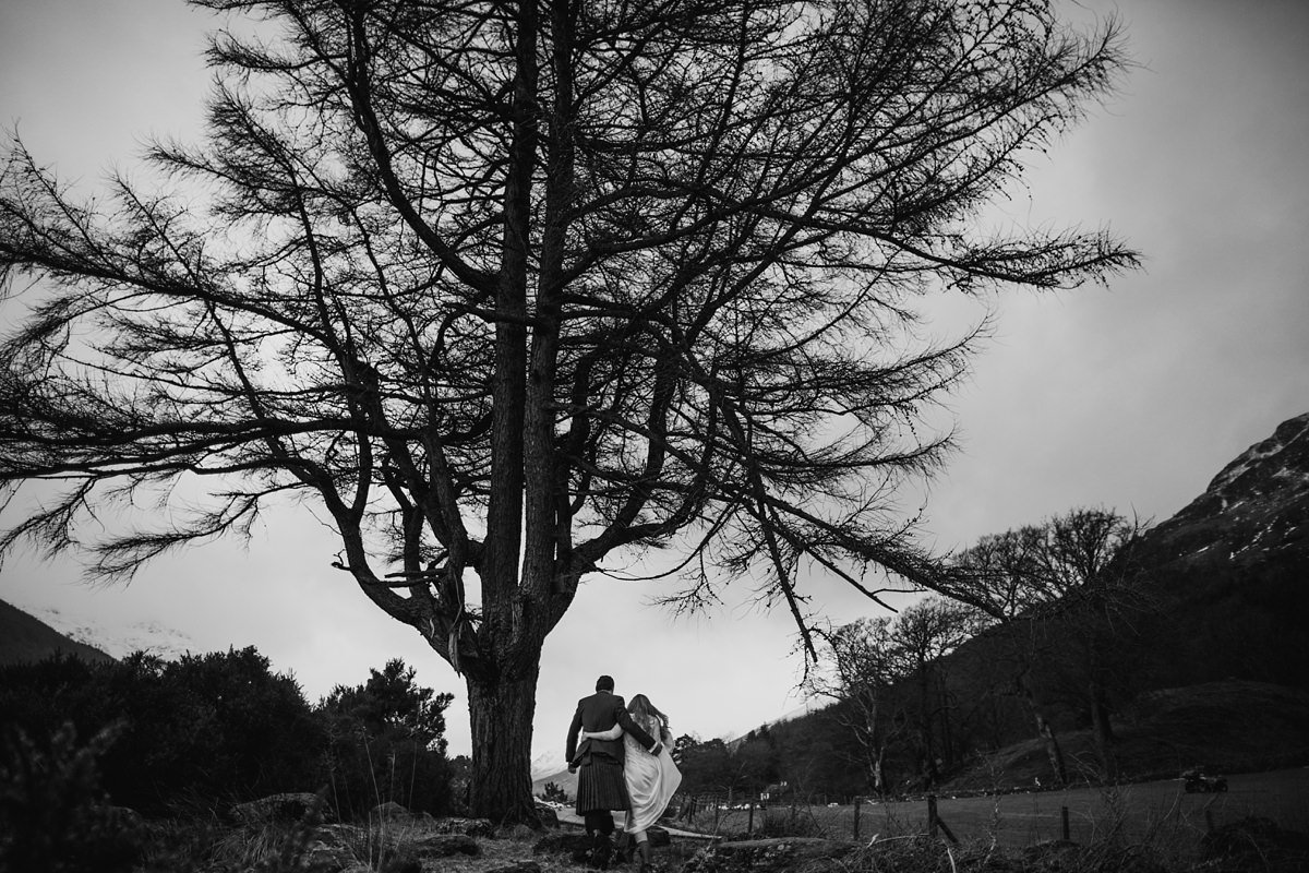 black and white of wedding couple walking under a tree