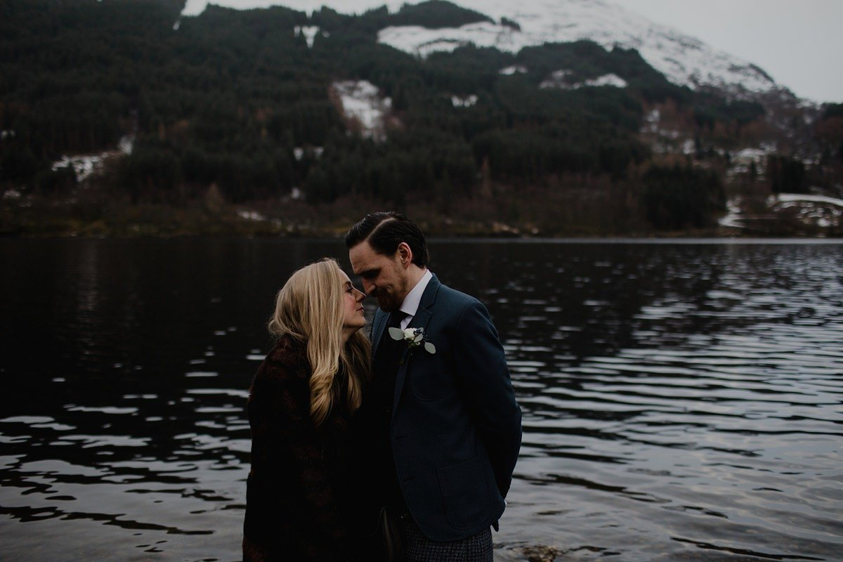 bride and groom by the water with snow dusted hills in background