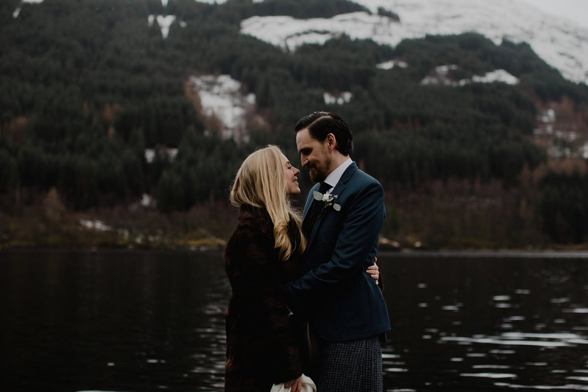 romantic portrait of wedding couple smiling by the lochside, winter wedding