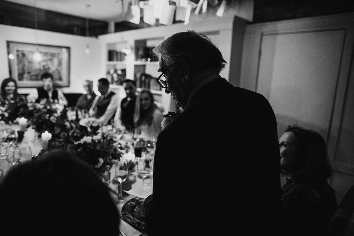 bride's dad doing his speech to the table of guests