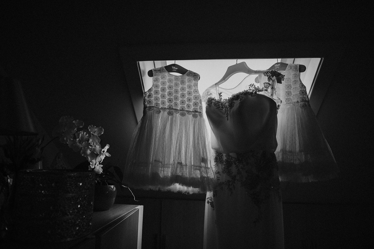 flower girl and wedding dress hanging in the window